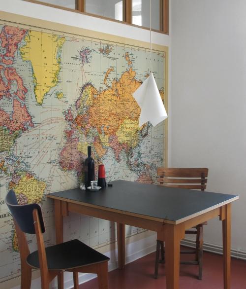 Fototapet med et verdenskort i retrofarver, som hænger på en væg over et spisebord.